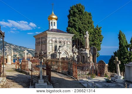 Old Russian orthodox chapel among crosses, statues and graves on old cemetery overlooking Mediterranean sea in Menton, France.