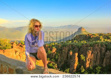 Young Tourist Sitting On The Rocks At Sunset After Trekking At Valley Of Desolation Near Graaff-rein