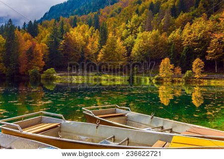 Boat station on the picturesque quiet lake Lago de Fusine in the mountain Alpine valley. The beautiful multu-colored forests. Concept of cultural and ecological tourism