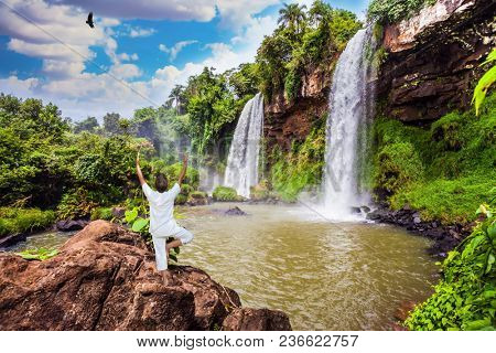 Two powerful fairy waterfalls from Iguazu Falls fall into a small quiet pond. The concept of extreme and ecological tourism. Elderly woman practicing yoga at the Iguazu Falls