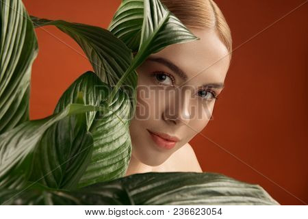 Eco Concept. Portrait Of Young Woman With Clean Pelt Looking Out Of Green Plant. Isolated On Backgro