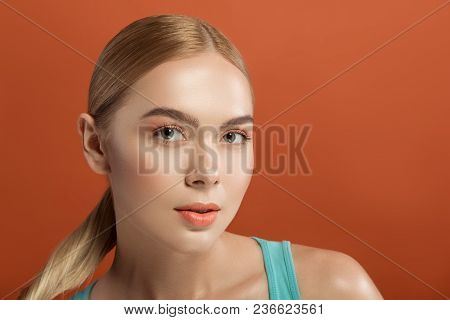 Portrait Of Young Female Face With Cared Skin And Straight Hair. She Is Looking At Camera With Calmn