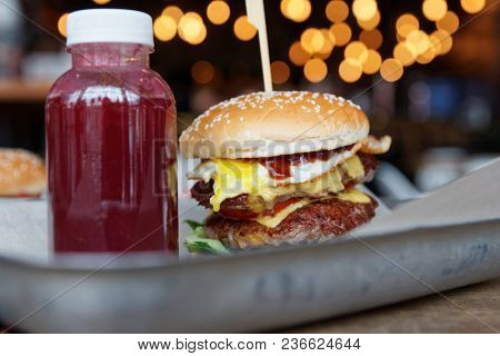 Burger and berry smoothie on metal tray close-up, fast food
