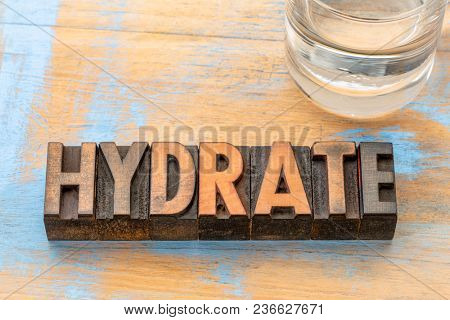 hydrate advice - word abstract in vintage letterpress wood type with a glass of water