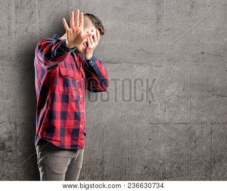 Young handsome man stressful and shy keeping hand on head, tired and frustrated