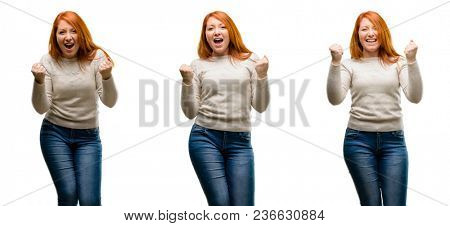 Young Beautiful redhead woman happy and excited expressing winning gesture. Successful and celebrating victory, triumphant