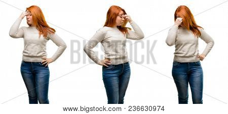 Young Beautiful redhead woman with sleepy expression, being overworked and tired, rubbes nose because of weariness