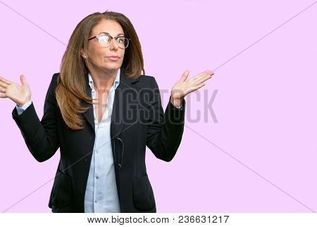Middle age business woman doubt expression, confuse and wonder concept, uncertain future shrugging shoulders