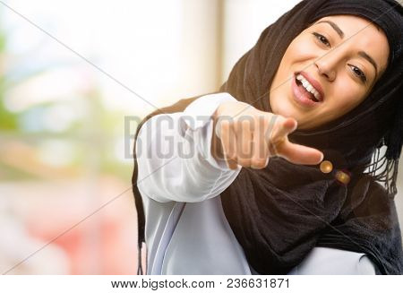 Young arab woman wearing hijab pointing to the front with finger