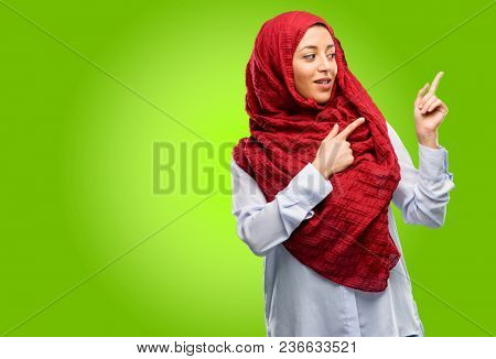 Young arab woman wearing hijab pointing away side with his finger