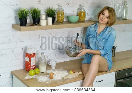 Young Attractive Girl Is Preparing Cookies In The Kitchen. She Holds A Rolling Pin And A Confectione
