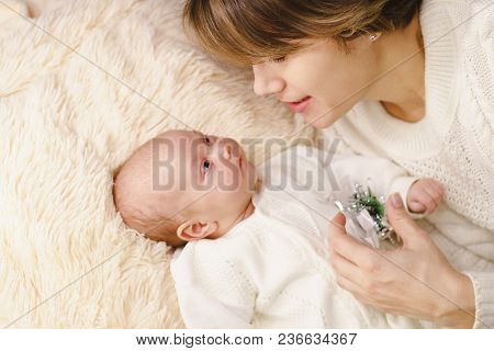 Mother And Newborn Daughter Lie On Pink Plaid. They Are Dressed In Warm Knitted White Sweaters. Moth