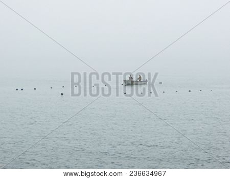 Aquaculture boat working in fog at plantation in the open sea poster