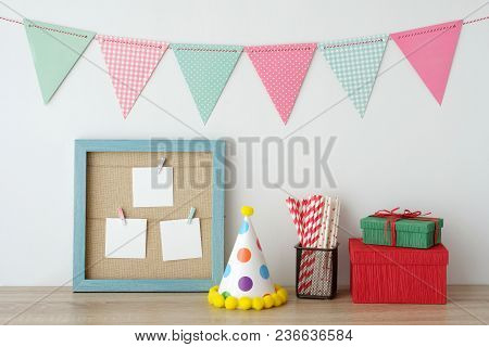 Colorful Party Flags Hanging Over Blue Vintage Wooden Frame With Blank Paper Cards And Gift Box, Par