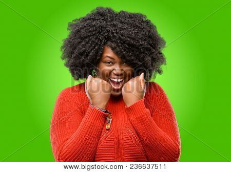 Beautiful african woman happy and excited expressing winning gesture. Successful and celebrating victory, triumphant