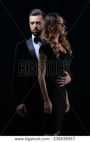 man next to woman posing in studio