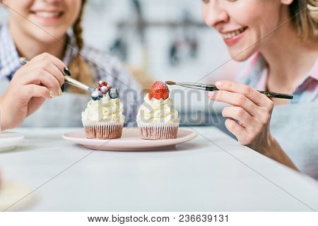 Close-up view of Caucasian women smiling cheerfully while decorating appetizing cream cupcakes with berries and frosting