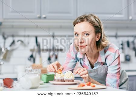 Portrait of attractive Caucasian woman decorating appetizing cupcakes with strawberries and smiling at camera
