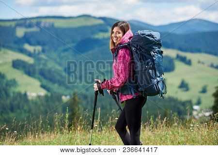 Portrait Of Beautiful Sporty Woman Hiker With Blue Backpack And Trekking Sticks, Hiking In The Mount