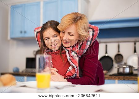 Little Pretty Girl Hugging Her Granny. Spend Time In The Kitchen. Family Dinner Concept.