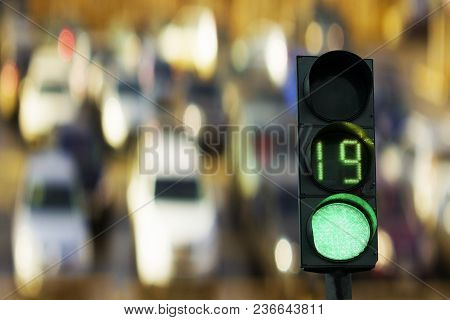 Traffic Light Green Signal On The Background Cars.