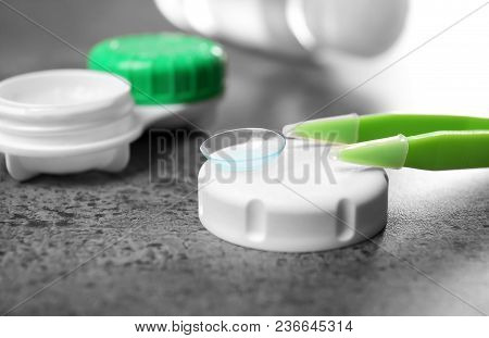 Contact Lens, Tweezers And Container Lid On Table, Closeup