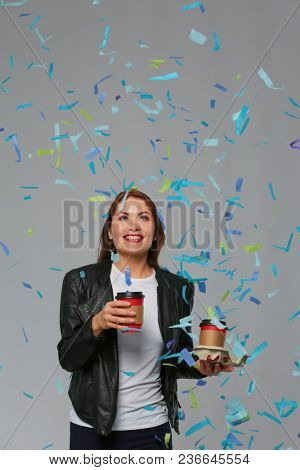 Beautiful happy woman with coffee at celebration party with confetti . Birthday or New Year eve celebrating concept