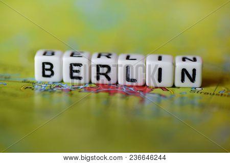 Word Berlin Formed By Alphabet Blocks On Atlas Map Geography