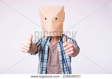 Unknown Man Showing Thumbs Up With A Paper Bag On His Head On White Background.