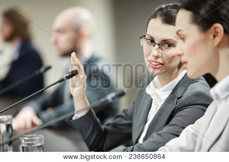 One of businesswomen covering mike by hand while consulting to her colleague or delegate