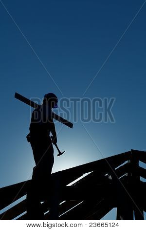 Builder Working Late On Top Of Building