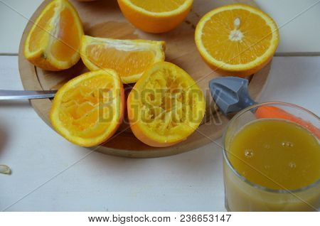 Some Oranges Are Cut In Half After Squeezing. A Glass Of Juice, Juicer, Half An Orange