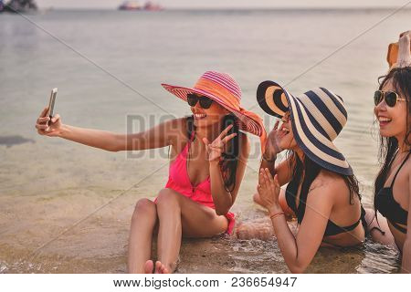 Swimsuit Concept. Beautiful Girl Wearing A Swimsuit Playing Mobile On The Beach. Beautiful Girl Is T