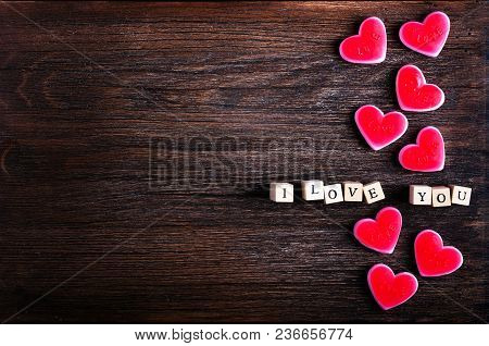 Heart Shaped Chewing Candies And Words I Love You On Cubes, Wooden Background. Free Space For Your T