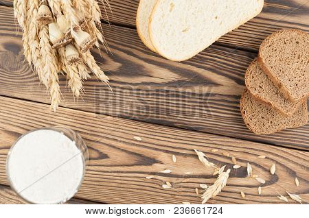 One Bundle Of Wheat And Poppy And Lot Of Scattered Grain And Slices Of Bread And Flour In Glass On O