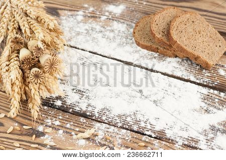 One Bundle Of Wheat And Poppy And Strewn Flour And Three Slices Of Bread On Old Rustic Wooden Planks