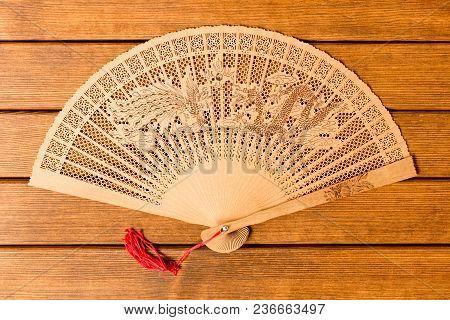 Beautiful Wooden Fan . On Old Wooden Background .