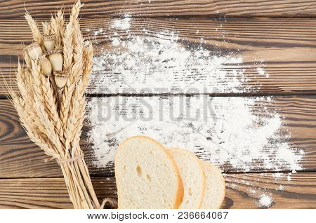 One Bundle Of Wheat And Poppy And Strewn Flour And Slices Of Bread On Old Rustic Wooden Planks