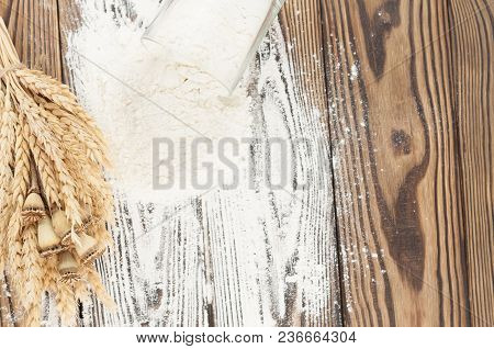 One Bundle Of Wheat And Poppy And Flour Poured Out Of Glass On Old Rustic Wooden Planks