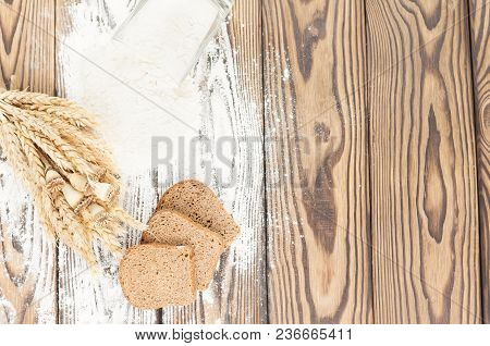 One Bundle Of Wheat And Poppy And Flour Poured Out Of Glass And Slices Of Bread On Old Rustic Wooden
