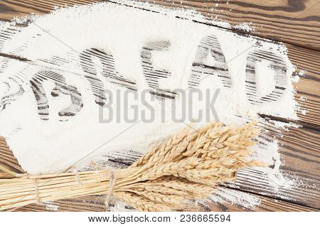 One Bundle Of Wheat And Poppy And Handwriting Word Bread On Flour On Old Rustic Wooden Planks