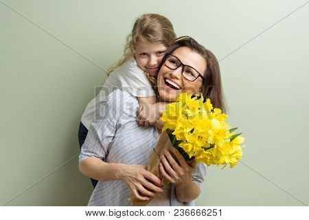 Child Daughter Congratulates Mother And Gives Her Bouquet Of Yellow Narcissus Flowers. Mom And Girl