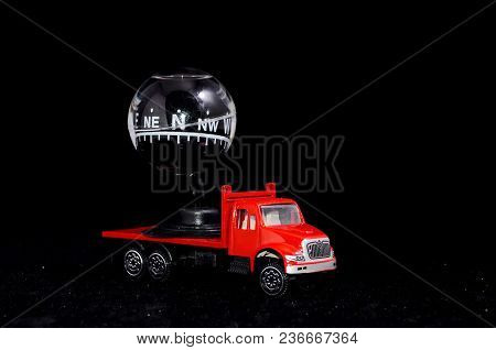 Orientation Transportation Concept Compass On A Red Toy Truck Over Black Background