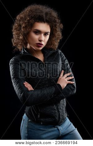 Confident Curly Girl Wearing Black Jacket And Blue Jeans. Model Having Curly Hair, Beatiful Face Wit