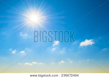 Sun With Bright Rays In The Blue Sky With White Light Clouds, At The Horizon A Yellowish Shade, A Gr