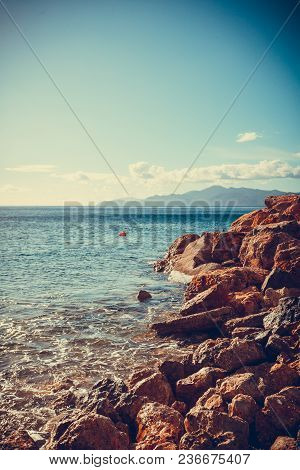 Beautiful Sea Landscape. Ocean Water Calmly Waving Next To Rock Coastline During Summer Warm Weather