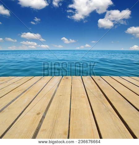 Wood, blue sea and sky background