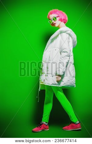 Full length portrait of a trendy girl with pink hair wearing bright stylish clothes. Green background. Beauty, fashion, youth style.