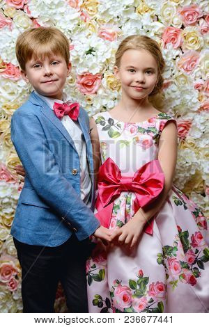 Children's fashion. Beautiful boy and girl in elegant clothes posing on a background of roses.