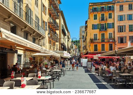 NICE, FRANCE - 02 SEPTEMBER, 2015: People sitting in outdoor restaurants on narrow street in Old town of Nice -  fifth most populous city in France, popular tourist destination.